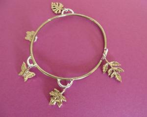 Armband brons met 5 bronzen bedels, bestaande uit verschillende blaadjes en vlinders. Op voorraad €150,00