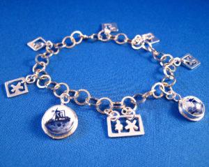 Zilveren armband ontworpen in opdracht n.a.v. de expositie. Deze armband is naast en uitgezaagde bedels uit plaatmateriaal ook voorzien van 2 bedels met een delftsblauw steentje.
