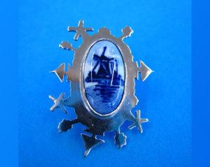 Broche gemaakt van alpaca met Delftsblauwe steen met daar omheen een Hollands landschap met boompjes, bootjes en molentjes. Op voorraad €85,00