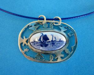 Ovale hanger gemaakt van alpaca met uitgezaagd Hollands landschap. Voorzien van Delftsblauwe steen.