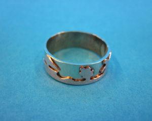 Ring gemaakt van alpaca en koper. Met koper is er een reliëf aangebracht van een Hollands landschap