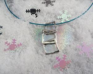 Zilveren hanger bestaande uit 3 lossen vierkantjes die aan elkaar zitten. Op verschillende manieren aan een spang te hangen. €95,00