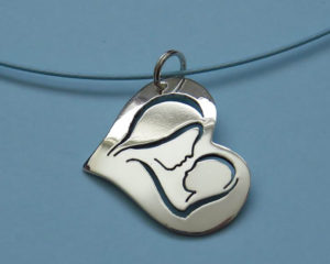 Zilveren hartvormige Moeder-Kind hanger. Moeder en kind is in de hartvorm uitgezaagd. Op bestelling €85,00