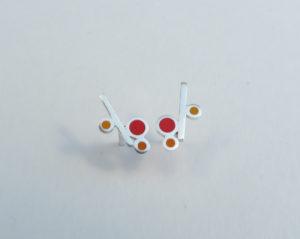Zilveren oorbelknopjes. Bestaande uit een staafje met 3 rondjes. deze zijn gevuld met rood en oranje kunststof. Op voorraad €65,00